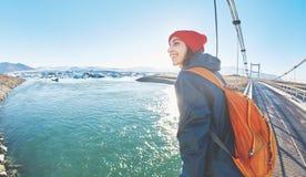 快乐的妇女在brige走在Jokulsarlon冰盐水湖 免版税库存照片