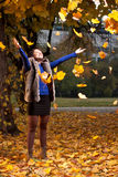 快乐的妇女投掷的秋叶 库存照片