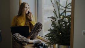 快乐的妇女摄影师谈的电话和在家坐与照相机和便携式计算机的窗台 库存图片