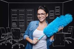 快乐的妇女清洁尘土 免版税库存图片