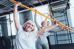 快乐的妇女用做边弯曲的锻炼的棍子在健身房 库存图片