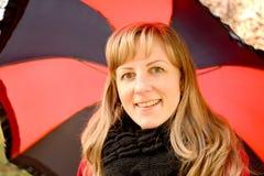 年轻快乐的妇女的画象以一把黑红色伞为背景的 免版税库存照片