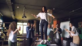 快乐的妇女跳舞的慢动作在桌上的在公司党的办公室,当她的同事站立时 股票视频