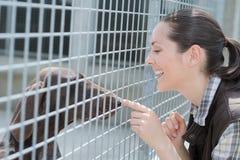 快乐的妇女通过篱芭给狗甜点 免版税库存照片