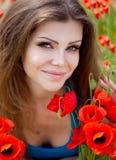 快乐的妇女画象室外与红色鸦片在她的手上开花 免版税图库摄影