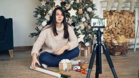 快乐的妇女vlogger记录关于礼品包装材料的讲解坐在圣诞树附近和拿着明亮的包装 股票录像