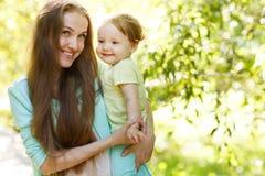 快乐的妈咪在夏天公园拥抱女孩 库存图片