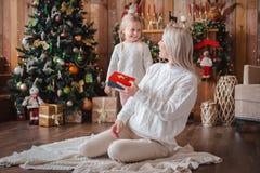 快乐的妈妈和她逗人喜爱的交换礼物的女儿女孩 库存图片