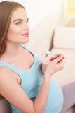 快乐的妊妇享用新鲜食品 免版税库存照片