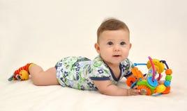 快乐的婴孩拿着在轻的背景的一个玩具 库存照片