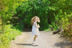 快乐的嬉戏的卷曲小女孩在森林里 库存照片