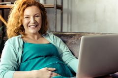快乐的孕妇与膝上型计算机一起使用 免版税图库摄影