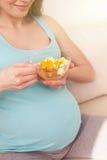 快乐的孕妇吃仅健康食物 库存图片