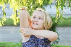 快乐的学校使用与金子坐立不安锭床工人的年迈的女孩 转动在手肘的一个普遍的时髦玩具 免版税库存图片