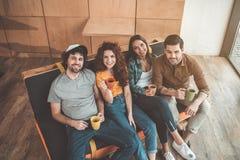 快乐的学生坐长沙发在休息室区域 免版税库存照片