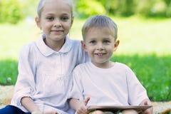快乐的孩子使用一台片剂个人计算机 免版税库存照片
