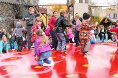 快乐的孩子跳在一张红色可膨胀的绷床的乐趣 库存照片