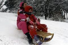 快乐的孩子sledding下来 免版税库存图片