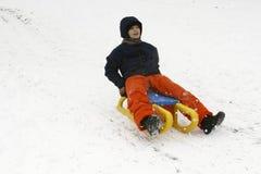 快乐的孩子sledding下来 图库摄影