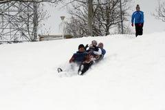 快乐的孩子sledding下来 免版税库存照片