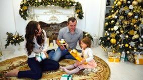 快乐的家庭假日愉快的诱惑本质一起和在欢乐树背景的大屋子里给礼物和 股票视频