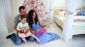 快乐的家庭有乐趣一起休闲、笑和微笑在假日树背景的宽敞卧室光和 股票录像