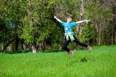 快乐的小女孩在草跳 免版税库存图片