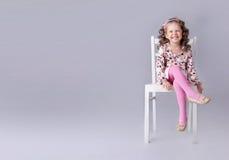 快乐的小女孩坐与微笑的椅子 免版税图库摄影