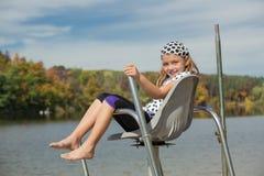 快乐的小女孩开会和放松在救生员椅子的水上 免版税图库摄影