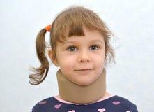 快乐的小女孩的画象有一个矫形衣领的 免版税库存照片