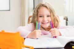 快乐的小女孩着色在桌上 免版税库存照片