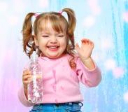 快乐的小女孩饮用水的纵向从瓶的 免版税图库摄影