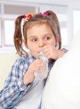 快乐的小女孩饮用水的纵向从瓶的 图库摄影