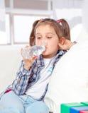 快乐的小女孩饮用水的纵向从瓶的 库存照片