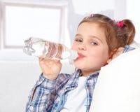 快乐的小女孩饮用水的纵向从瓶的 免版税库存图片