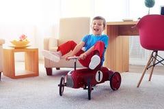 快乐的小男孩坐红色减速火箭的玩具汽车 图库摄影