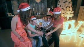 快乐的小组在圣诞节附近的朋友装饰了树,从酒杯的饮料酒精-笑,获得乐趣 股票录像
