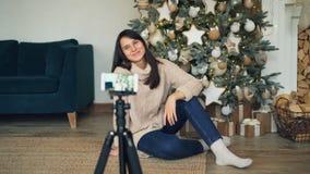 快乐的少女在装饰的圣诞树附近记录录影开会并且看在三脚架的智能手机照相机 股票视频