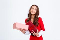 快乐的少妇在圣诞老人服装藏品打开了礼物 库存照片