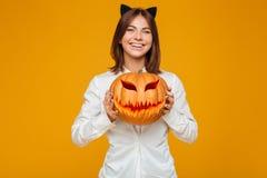 快乐的少妇在疯狂的猫万圣夜服装穿戴了 库存图片