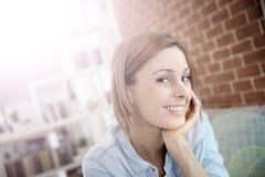快乐的少妇坐长沙发 免版税库存照片