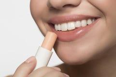 快乐的少妇应用卫生唇膏 免版税图库摄影