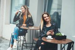 快乐的少妇微笑和拿着智能手机的室外饮用的咖啡手中与美丽的时兴的女孩坐bac 库存图片