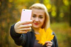快乐的少妇画象有秋天的在做selfie的叶子前面生叶 免版税库存照片