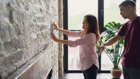 快乐的少妇选择被构筑的照片的地方砖墙的,当她的丈夫帮助她时,愉快 影视素材