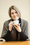 快乐的少妇饮用的咖啡在桌上 库存照片