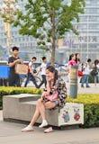 快乐的少妇ona长凳,北京,中国 库存照片