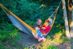 快乐的少年-兄弟和姐妹在吊床乘坐 库存图片