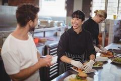 快乐的工作在厨房里的侍者和女性厨师 库存照片