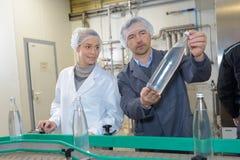 快乐的工作在啤酒厂工厂的男人和妇女 免版税库存照片
